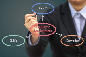 Businessman writing Employee development concept.